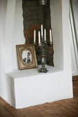 White candles in five-armed candelabra and vintage photo on masonry plinth