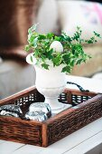 Stone urn of ivy and egg ornament on tray with wicker edge