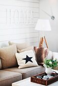 Sofa with scatter cushions below letters spelling 'Home' on white wooden wall
