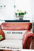 Pale upholstery printed with 'AT HOME' motif on backrest and seat of traditional leather lounge chair