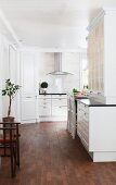 Open-plan, white, country-house kitchen with ample storage space and dark wooden floor