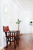 Classic, wooden folding chair with leather inserts below round mirror