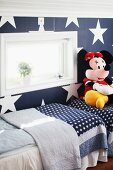 Twin beds and large Minnie Mouse soft toy in blue and white children's bedroom with patterns of stars on beds and wall