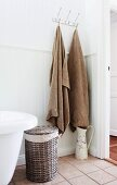 Bath towels hanging from hooks, old water jug with floral motif and laundry basket in country-house bathroom