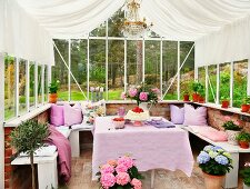 Dining area decorated in shades of lilac with U-shaped bench in conservatory
