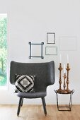 Armchair with scatter cushion next to set of candlesticks on side table below washi tape picture frames on wall