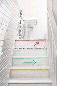 Wooden staircase in narrow stairwell with white, wood-clad walls; treads edged with colourful washi tape and washi tape arrows