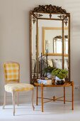Rococo chair with white and yellow gingham upholstery next to side table below mirror with ornate frame