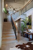 Staircase in open-plan foyer with animal-skin rug, antique console table and potted palms