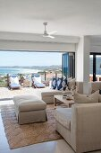 Ecru sofa set with ottoman and chaise in front of open folding doors with view onto sunny terrace