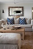 Ecru ottoman and sofa with scatter cushions around pale wooden coffee table below mirror with rustic wooden frame