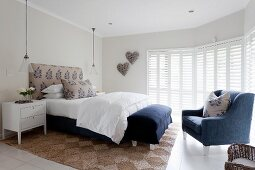 Elegant white bedroom with blue accents, blue armchair and blue bench at foot of bed