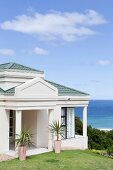 Potted palms in front of veranda of whitewashed, Colonial-style villa with sea view