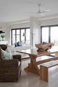 Modern bench, wooden table and wicker armchair in open-plan interior