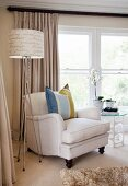 Pale armchair with striped scatter cushion next to standard lamp with lettering on lampshade