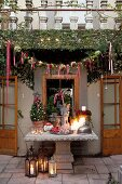 Festively decorated house and terrace with antique stone table and floor lanterns
