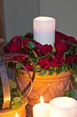 White candle in pot of roses lit by candles