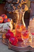 Refreshing drinks and pomegranates on vintage silver tray