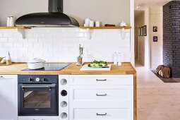 Kitchen counter with wooden worksurface and built-in cooker below extractor hood next to cabinet with white drawer fronts
