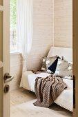 View through open door of blanket on sofa in corner of room with pale, varnished wooden walls