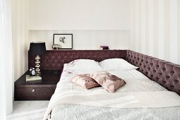 A double bed with a built-in bedside table in an elegant bedroom with a brown velvet headrest running around one side