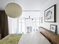 Bedspread on double bed below spherical lamp in bedroom with glass wall