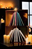 Magazines arranged in shape of Christmas tree in wooden crates with straw star and lit candles