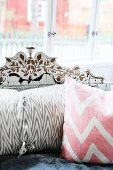 Delicately painted backrest of vintage sofa with modern scatter cushions in pastel shades