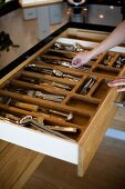 Open wooden cutlery drawer with divisions