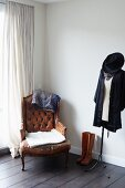 Antique leather armchair, boots and clothing on tailors' dummy in corner