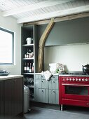 Kitchen with red, retro gas cooker and grey-painted cabinets in rustic interior