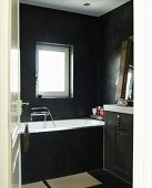 Black-painted bathroom with washstand and bathtub below window