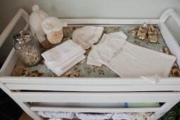 Detail of baby clothes on white trolley