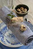 Place setting with blue and white crockery, quail eggs on napkin and name card