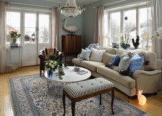 Traditional living room with pale sofa, many scatter cushions and bunny-shaped floor lamp