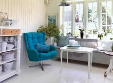 Open-fronted crockery cabinet next to swivel armchair with blue upholstery and white side table in front of bench below window