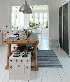 Toy cooker in front of old workbench used as kitchen counter in Scandinavian kitchen-dining room with white wooden floor