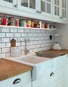 White kitchen counter with ceramic sink and splashback with subway tiles below wall-mounted units