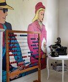 Vintage abacus next to antique telephone and typewriter on side table in front of pop art mural on wall