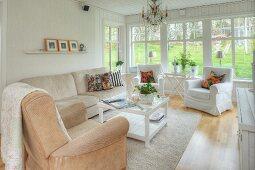 Wohnzimmer mit hellen Polstermöbeln, Kristallkronleuchter und Fensterfront