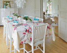 Festlich gedeckter Tisch mit floral gemusterter Decke im weissen Esszimmer