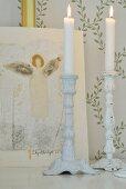 weiße Kerzenhalter und Engelsbild vor Tapete mit zartem Blattranken-Muster