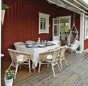 Gedeckter Tisch mit Rattansesseln und Hängestuhl auf der Veranda eines Schwedenhauses
