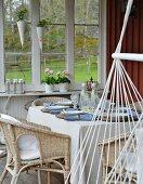 Korbstühle an gedecktem Tisch und Hängestuhl auf Holzveranda