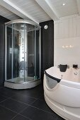 Modern shower cabinet and whirlpool bathtub in black and white bathroom in Scandinavian wooden house