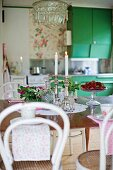 White Thonet chairs at table, lit candles in silver candlestick and bowl of fresh strawberries