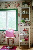 Thonet chair below window next to side table and cabinet mounted on wall with floral wallpaper