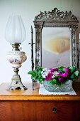 Paraffin lamp and bowl of flowers in front of vanity mirror with ornate silver frame on simple wooden chest of drawers
