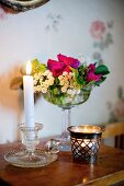 Lit candle in vintage, glass candlestick next to tealight holder in front of dish of flowers