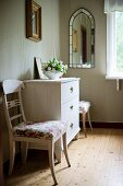 Upholstered, white-painted kitchen chairs flanking chest of drawers in rustic interior with well-tended wooden floor